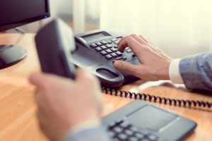 Businessman dialing on VOIP Phone