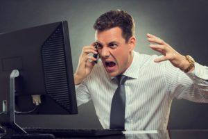 Angry businessman yelling at an IT helpdesk person on the phone in front of a broken desktop computer.