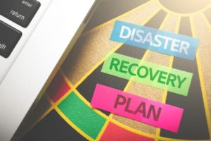 Disaster Recovery Plan shown on a dart board next to a laptop