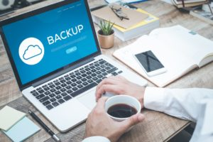 Backups and Data Recovery concept on laptop with business man drinking coffee