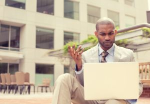 Business man in summer heat on laptop wishing he had a Backup Disaster Recovery (BDR) plan