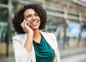 Business woman using VOIP in a mobile phone out outdoors
