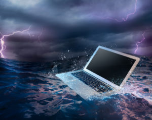 Backup Disaster Recovery (BDR) Plan concept with laptop on water
