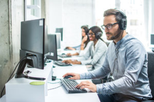 Young male customer support executive working IT help desk
