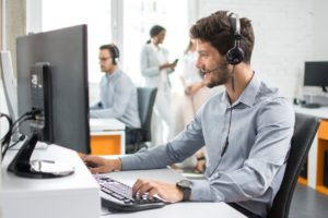 Smiling handsome customer support operator agent making VOIP calls on a nice headset with a good quality microphone with hands-free device working in call center