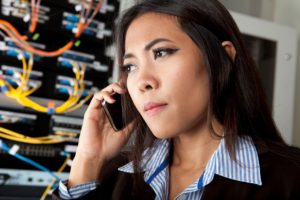 Woman in a server room on phone preparing a backup disaster recovery plan
