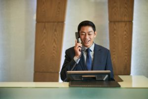 Male receptionist calling an IT help desk in a hotel