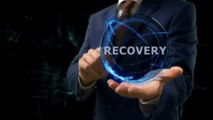 Businessman shows concept hologram Recovery on his hand. Disaster recovery preparation concept