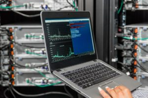IT Engineer Using Laptopf for Network Monitoring and Analysis of Network Servers in Server Room
