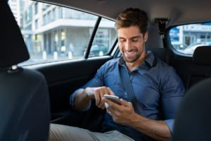 Business man in a car using VOIP to make and receive calls from the same number