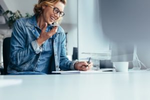 Business woman at her desk, on speaker phone with her managed service provider