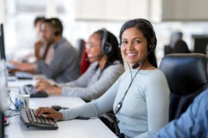 Confident female operator with a headset is working with colleagues at desk in an IT help desk call center