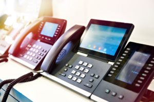 Voice-over-IP (VoIP) phones in a row in an office desk