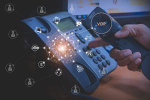 Hand of man using ip phone with flying icon of voip services and people connection, voip and telecommunication concept