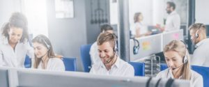IT help desk worker accompanied by his team. Smiling customer support operator at work. Young employee working with a headset.