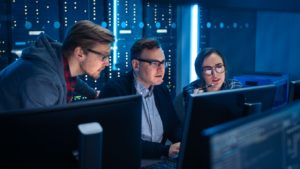 Three IT managers work together on technical projects