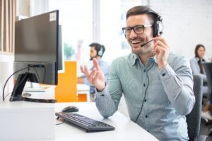 A happy male technical support operator working in an IT help desk call center setting speaking and assisting a customer online and speaking through a headset.